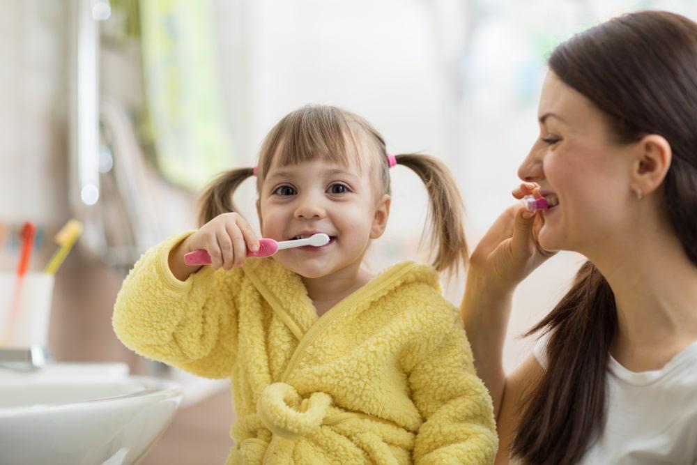 Un mère et sa fille font leur hygiène dentaire