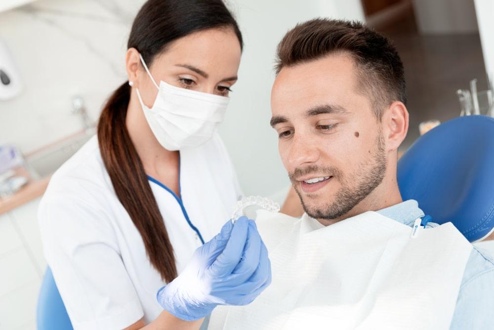 dentiste qui présente un traitement d'orthodontie à un homme adulte